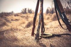 Escena de la caza con las escopetas de la caza y la correa de la munición en hierba seca en campo rural durante temporada de caza Imágenes de archivo libres de regalías