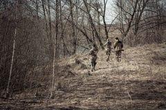 Escena de la caza con los cazadores en camuflaje que roban en bosque de la primavera con las hojas secas durante temporada de caz Fotos de archivo libres de regalías