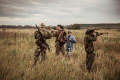Escena de la caza con los cazadores que apuntan durante temporada de caza en campo rural en día cubierto con el cielo cambiante Fotografía de archivo libre de regalías