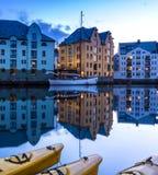 Escena de la ciudad con las casas tradicionales y los barcos reflejados en un canal tranquilo en la noche en Alesund imagen de archivo libre de regalías