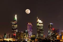 Escena de la ciudad con la luna que sube sobre el distrito financiero central de Ho Chi Minh City por noche imagen de archivo