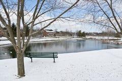 Escena de la ciudad del invierno con un banco cerca de la charca Fotografía de archivo libre de regalías