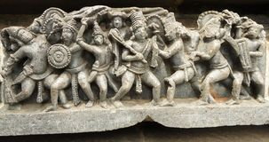 Escena de la guerra - tallas en piedra en Belur Foto de archivo