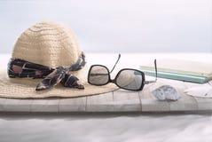 Escena de la lectura en la playa con el sombrero y las gafas de sol imagen de archivo libre de regalías