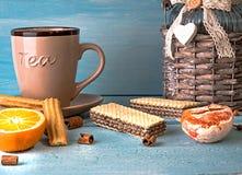 Escena de la mañana con la taza de té o de café, stroopwafel holandés de la galleta, recuerdo azul de las cerámicas de Delft, en  Foto de archivo