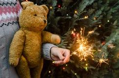 Escena de la Navidad - oso y bengala de peluche de la tenencia de la mujer antes del árbol de navidad imagen de archivo