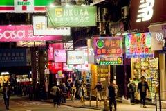 Escena de la noche con la muchedumbre de gente y de carteleras que caminan de tiendas Imágenes de archivo libres de regalías