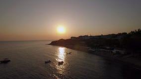 Escena de la puesta del sol del centro turístico y del mar con los barcos, aérea Playa de Trikorfo en Grecia almacen de metraje de vídeo