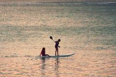 Escena de la puesta del sol en fondo Dos siluetas de las niñas padddling fotos de archivo