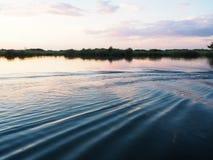 Escena de la puesta del sol en la orilla del río con la ondulación y la reflexión del agua Fotos de archivo libres de regalías