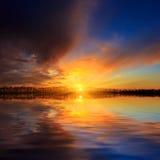 Escena de la puesta del sol sobre superficie del agua del lago Foto de archivo