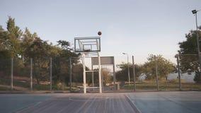 Escena de un jugador de básquet de sexo femenino que practica en lanzar la bola al aro en la cancha de básquet del local al aire  almacen de video