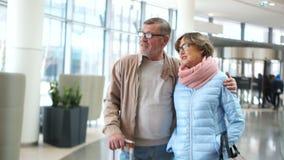 Escena del aeropuerto de los pares que viaja mayores Hombre y mujer en esperar su vuelo que mira en la distancia vestido metrajes