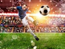 Escena del f?tbol en el partido de la noche con el jugador que golpea la bola con el pie con poder imagen de archivo libre de regalías