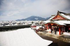 Escena del invierno de la gente que ruega en un templ japonés Fotos de archivo libres de regalías