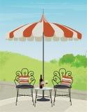 Escena del jardín del patio trasero con las sillas del hierro labrado y el paraguas rayado Imagenes de archivo
