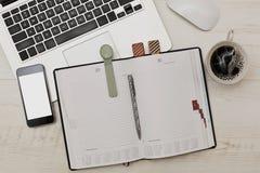 Escena del negocio con el diario, el ordenador portátil y la célula Fotografía de archivo libre de regalías