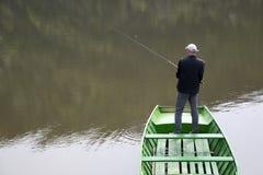 Escena del pescador With His Back hacia la pesca de la cámara del barco en el lago tranquilo Imagen de archivo libre de regalías