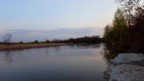 Escena del r?o de la ma?ana con Canoers en el fondo durante d?a Agua del canal de la orilla que fluye con la gente en una canoa e