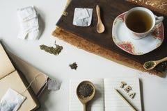 Escena del té del vintage con la taza y platillo, tabla de cortar, cucharas y libro de la nota fotos de archivo libres de regalías
