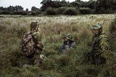 Escena dramática de la caza con el grupo de cazadores en campo rural en la expectativa de la caza en hierba alta durante temporad Foto de archivo