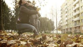 Escena dulce de la familia: el hijo trae un ramo hermoso de hojas otoñales a su madre almacen de metraje de vídeo