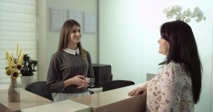 Escena en la oficina del dentista en donde el dentista discute el tratamiento con el paciente sonriente de la mujer que es relaja almacen de video