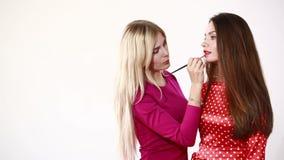 Escena entre bastidores: Artista de maquillaje profesional que hace el maquillaje modelo del encanto en el trabajo almacen de metraje de vídeo