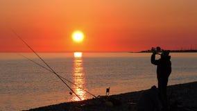 Escena hermosa con la silueta del pescador con la barra que se sienta en la playa del mar almacen de metraje de vídeo