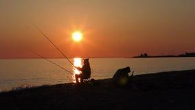 Escena hermosa con la silueta del pescador con la barra que se sienta en la playa del mar almacen de video