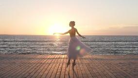 Escena hermosa de la cámara lenta de la bailarina joven que gira en un piso de madera al aire libre en la cámara lenta La playa,  almacen de metraje de vídeo