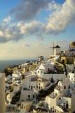Escena hermosa de la luz de la tarde del townscape blanco del edificio de Oia a lo largo de la montaña de la isla, del Mar Egeo,  Foto de archivo libre de regalías