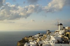 Escena hermosa de la luz de la tarde del townscape y del molino de viento blancos del edificio de Oia a lo largo de la montaña de Imagen de archivo libre de regalías