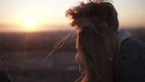 Escena hermosa del cople joven en el tejado durante la puesta del sol Paseos del hombre y unirse a su novia de la parte posterior almacen de metraje de vídeo