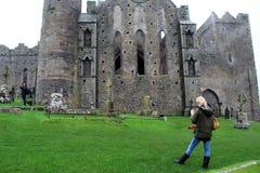 Escena magnífica con los turistas que dan un paseo alrededor de la roca histórica de Cashel, condado Tipperary, Irlanda, octubre  Foto de archivo libre de regalías