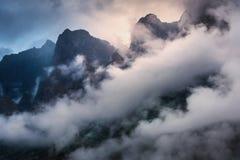 Escena majestuosa con las montañas en nubes por la tarde cubierta Foto de archivo