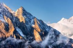 Escena majestuosa con las montañas con los picos iluminados por el sol en nubes en Nepal Paisaje Imágenes de archivo libres de regalías