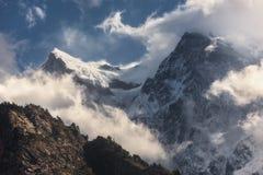 Escena majestuosa con las montañas con los picos nevosos en nubes Foto de archivo libre de regalías