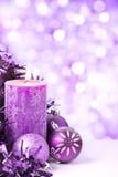 Escena púrpura de la Navidad con las chucherías y las velas Foto de archivo