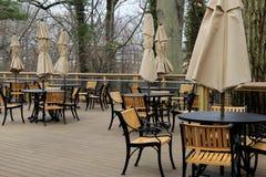 Escena pacífica de tablas y de sillas con los paraguas atados en patio al aire libre del restaurante Imagenes de archivo