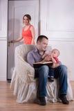 Escena, padre e hijo de la familia sentándose en acogedor foto de archivo libre de regalías