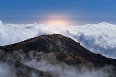 Escena que sorprende del pico de montaña y de nubes densas contra el cielo y la luz del sol de color naranja imágenes de archivo libres de regalías