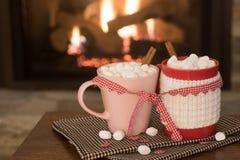 Escena romántica de la chimenea del día del ` s de la tarjeta del día de San Valentín con las tazas rojas y rosadas del cacao ata Fotografía de archivo