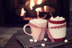 Escena romántica de la chimenea del día del ` s de la tarjeta del día de San Valentín con las tazas rojas y rosadas del cacao ata Foto de archivo libre de regalías