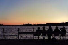 Escena romántica de la puesta del sol que mira en la costa del lago foto de archivo