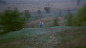 Escena romántica del día de niebla de los pares en el camino almacen de metraje de vídeo
