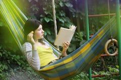 Escena serena con la muchacha adolescente en hamaca con el libro de lectura del albaricoque Fotografía de archivo libre de regalías