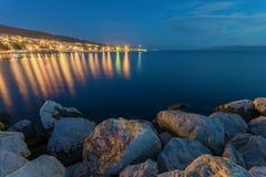 Escena tranquila de la pequeña ciudad por el mar en la noche Imagen de archivo libre de regalías