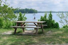 Escena tranquila de la tabla de madera con dos bancos en la costa del lago imagenes de archivo