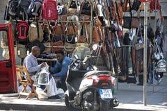 Escena urbana: hombres bicolores que venden los bolsos en la calle Foto de archivo libre de regalías